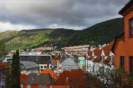 Picturesque view of Bergen. Mountains, clouds, sunlight and shadows, cityscape, rooftops. Hordaland, Norway. Stock fotó