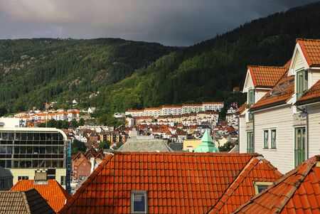 Picturesque view of Bergen. Mountains, clouds, sunlight and shadows, cityscape,tiled roofs. Hordaland, Norway.