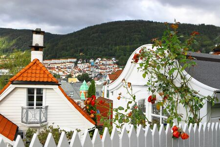 Beautiful view of Bergen in late summer. Mountains, clouds, sunlight and shadows, traditional wooden houses with tiled roofs, roses in the garden. Hordaland, Norway.