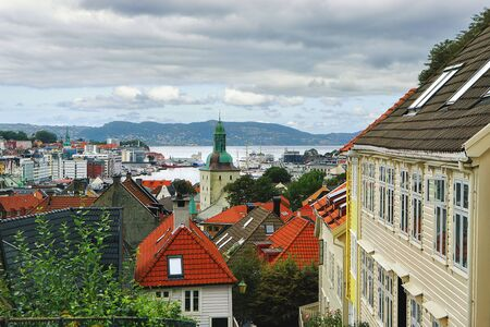 Beautiful view of Bergen in late summer. Bergen Domkirke Cathedral, mountains, clouds, harbor, traditional wooden houses with tiled roofs. Hordaland, Norway.