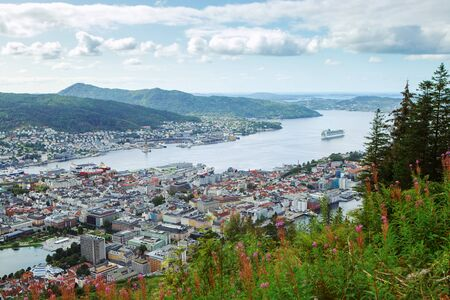 Famous view of Bergen from Mount Floyen in summer. Clouds, fjord, mountains, cityscape, yachts and ships. Landmark of Norway.
