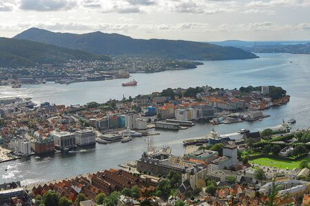Famous view of Bergen harbor from Mount Floyen in summer. Clouds, fjord, mountains, city center, yachts and ships. Landmark of Norway.