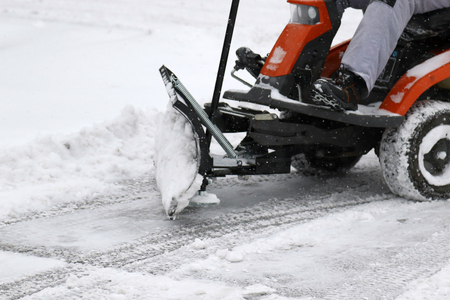 Riding snow mower and  removing snow from a parking lot Reklamní fotografie