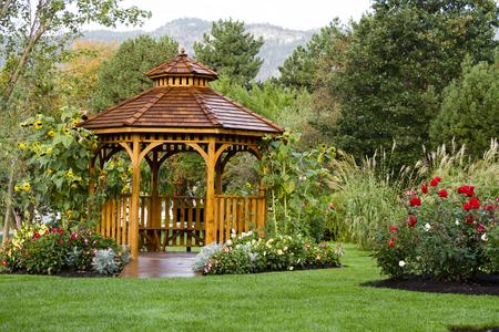 entrance arbor: Cedar gazebo in city park. Stock Photo