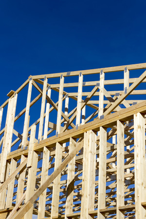 Wood construction frame of housing development detached house construction site using lumber stud construction material. The construction material is made by the lumber industry and used in the construction industry.
