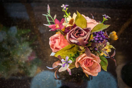 Beautiful colors of plastic flowers on granite table