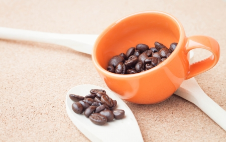 Coffee bean in ceramic cup and wood spoon photo
