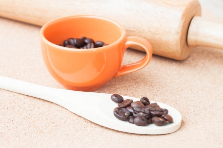 Roast coffee bean in a cup and wood spoon photo
