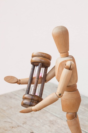 time critical: Wood mannequin and hourglass display time management