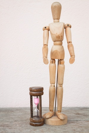 Wood mannequin and hourglass to represent spending time photo