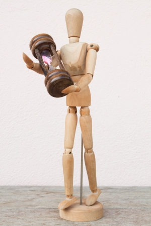 Wood mannequin and hourglass to represent time caring photo
