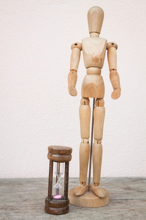 Wood mannequin and hourglass to represent time over photo
