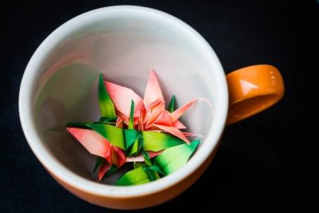 Mug cup of paper birds on dark background