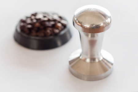 tamper: Coffee tamper and middle roasted coffee bean