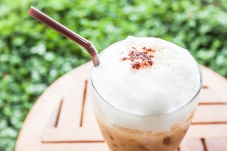 Refreshing glass of iced blended espresso with milk foam