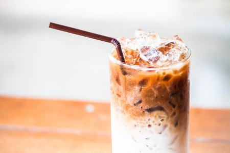 A glass of milk coffee with ice cubes