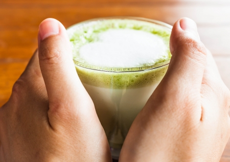 Hands hold hot drink of matcha green tea latte photo