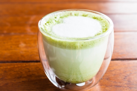 Hot matcha green tea latte glass with milk microfoam
