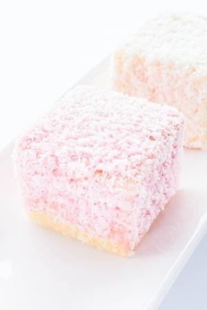 lamington: Lamington sponge cakes on white plate, stock photo