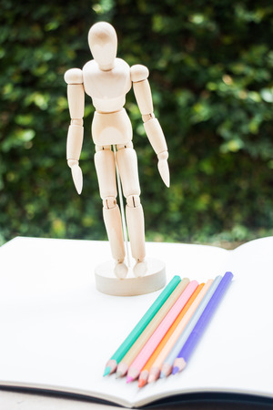 artists dummy: Wood mannequin standing on artist drawing paperbook