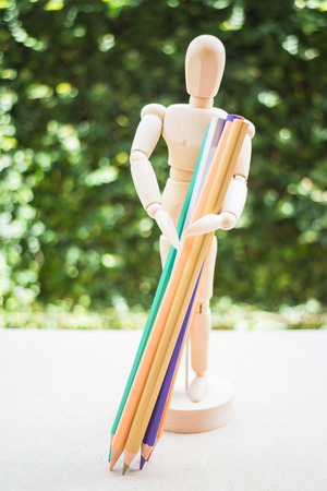 artists dummy: Wooden manikin carrying colour pencil on artist work table