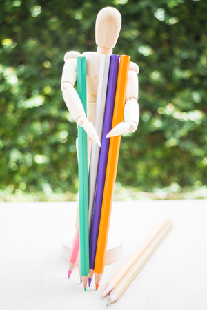 artists dummy: Wood artist mannequin standing with colour pencil