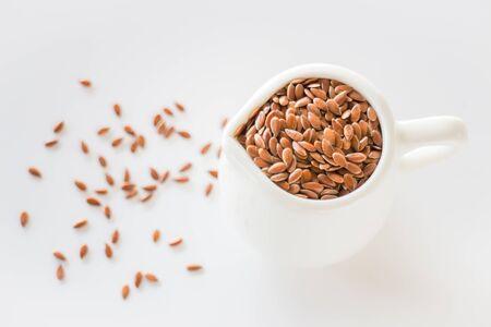 flaxseed: Pitcher of organic brown flaxseed, stock photo
