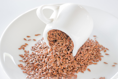 flaxseed: Organic brown flaxseed heap on white background, stock photo