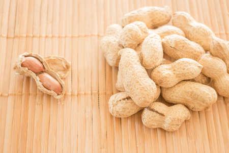 earthnuts: Salted peanuts on kitchen bamboo mat Stock Photo