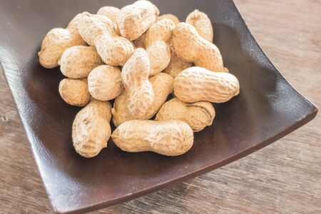 earthnuts: Salted peanuts on wooden bow, stock photo