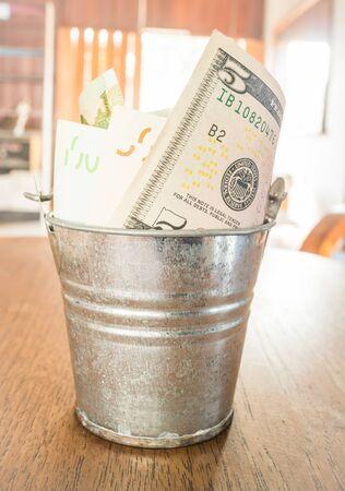 bucket of money: International currencies bank note in the bucket
