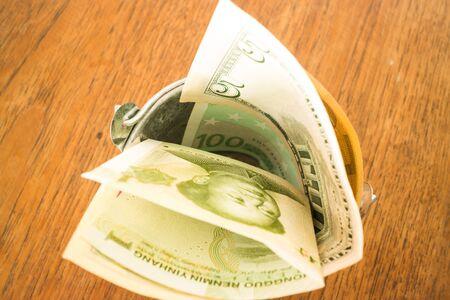 bucket of money: International currencies bank note in the bucket, stock photo