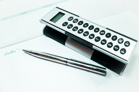 bank records: Pocket calculator and pen on the table, stock photo