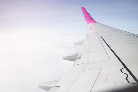mile high holidays: Airplane wing flying above the clouds sunset, stock photo