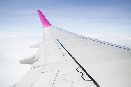 mile high holidays: Airplane wing flying above the clouds, stock photo