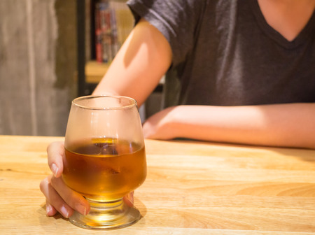 chilled out: Woman having alcoholic drink in the bar, stock photo