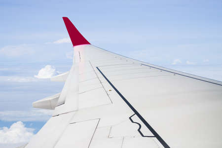mile high holidays: Plane wing on cloudy blue sky background, stock photo