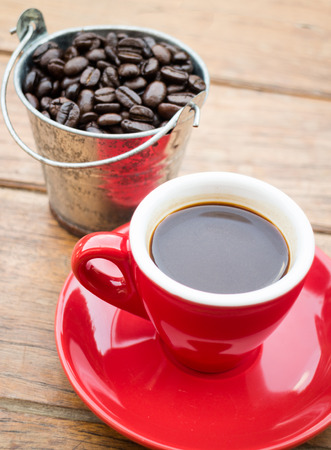 Red cup of espresso on wooden table, stock photo