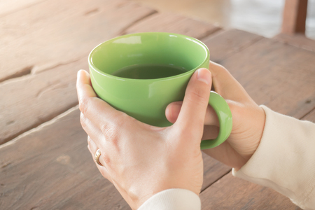 chilled out: Woman hand on hot green tea drinking, stock photo Stock Photo