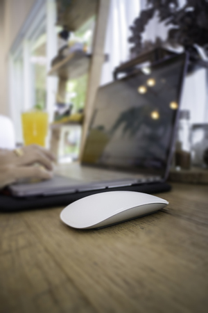 Woman with laptop and orange juice at table, stock photo Standard-Bild