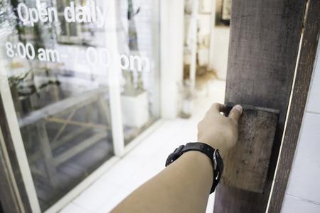 Woman hand opening shop door, stock photo