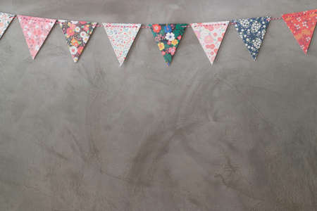 Triangle papers hanging on the grey wall decoration in house, stock photo Standard-Bild