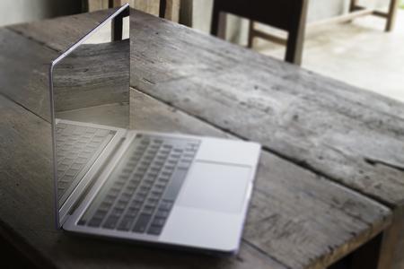 Modern grey metal laptop on wooden table, stock photo