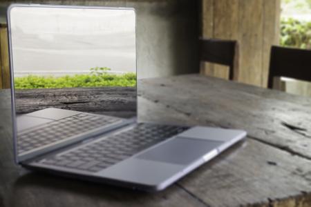 Moderner grauer Metalllaptop auf Holztisch, Foto auf Lager