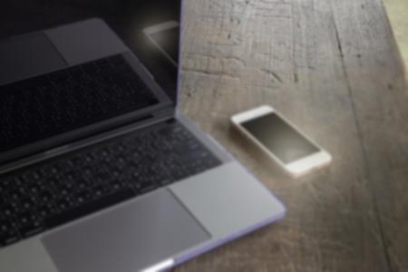 Modern grey metal laptop and smart phone on wooden table, stock photo Standard-Bild