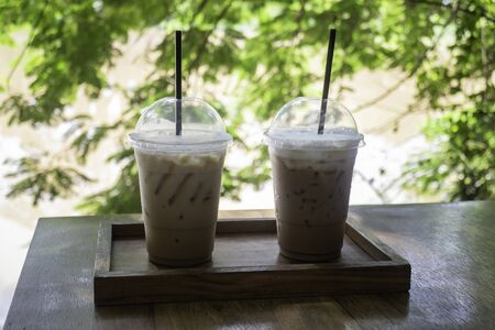 Iced coffee on wooden outdoors table, stock photo