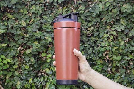 Aluminum mug on hand with green leaves wall, stock photo Standard-Bild