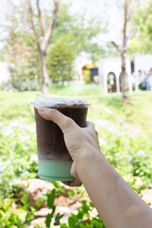Female hand holding iced coffee drink in disposable take away cup, stock photo Stockfoto