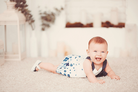 clean carpet: Beautiful little baby girl lies on a light carpet in the room Stock Photo