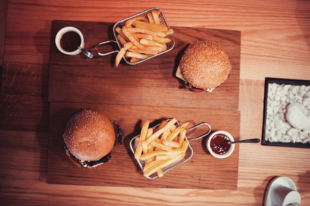 medium group of objects: fast food set big hamburger and french fries with wine. shallow DOF